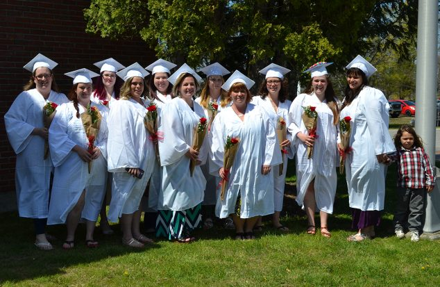 Graudates standing in white gowns