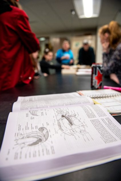 An open biology textbook in the foreground of a classroom
