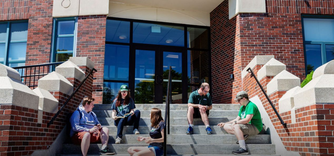 Students sitting on the front steps of a library
