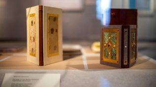 Ornately bound books in a glass case
