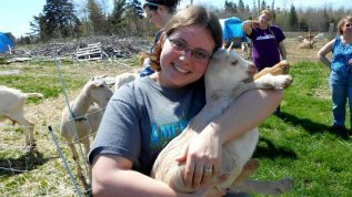 A student holding a baby goat