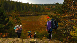 Students with hiking gear standing on rocky outcropping