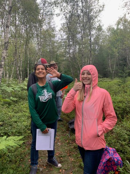 Students smiling and giving a thumbs up on a walk in the forest