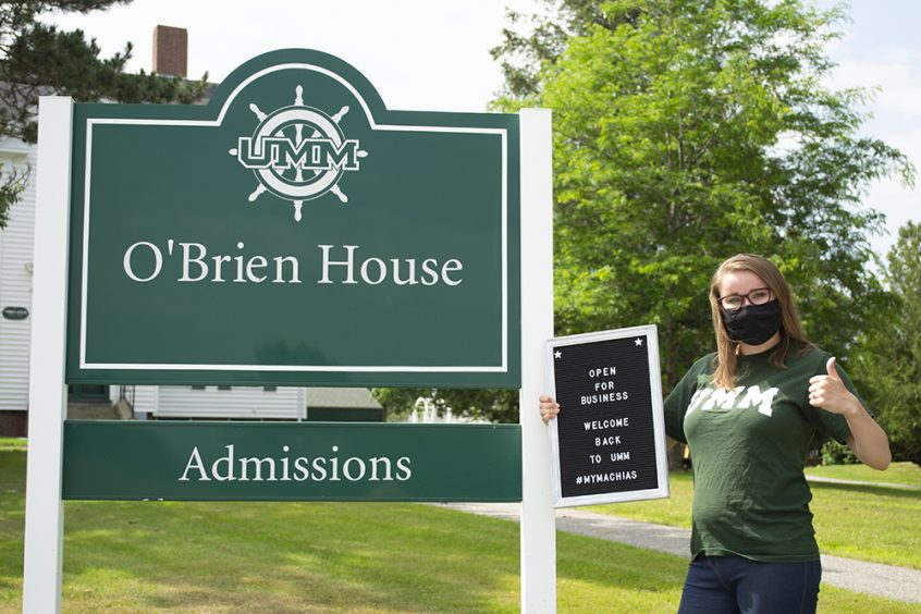 An admissions counselor standing in front of the OBrien House, holding a Welcome Back sign