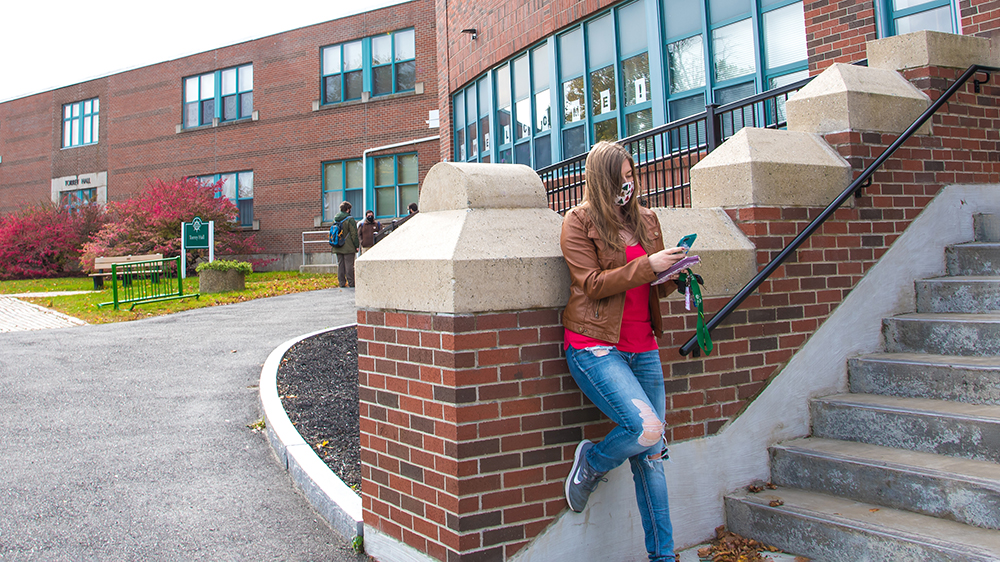 A student looking at her cellphone in front of a brick building