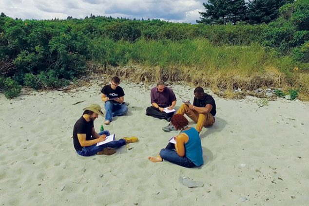 Four students and a professor sitting in the sand on a beach, in an outdoor writing workshop