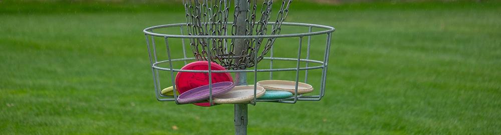 Metal disc golf basket in a grass field