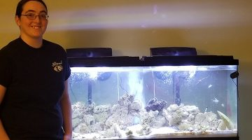 Aisling Farragher-Gemma poses next to a fish tank