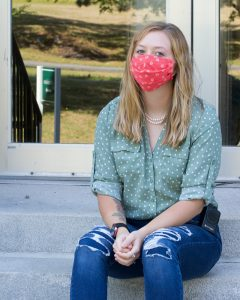A female student is seated on concrete steps. She is wearing an orange cloth face mask