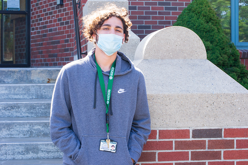 A young man in a hoodie is shown wearing a surgical mask in front of a brick entryway