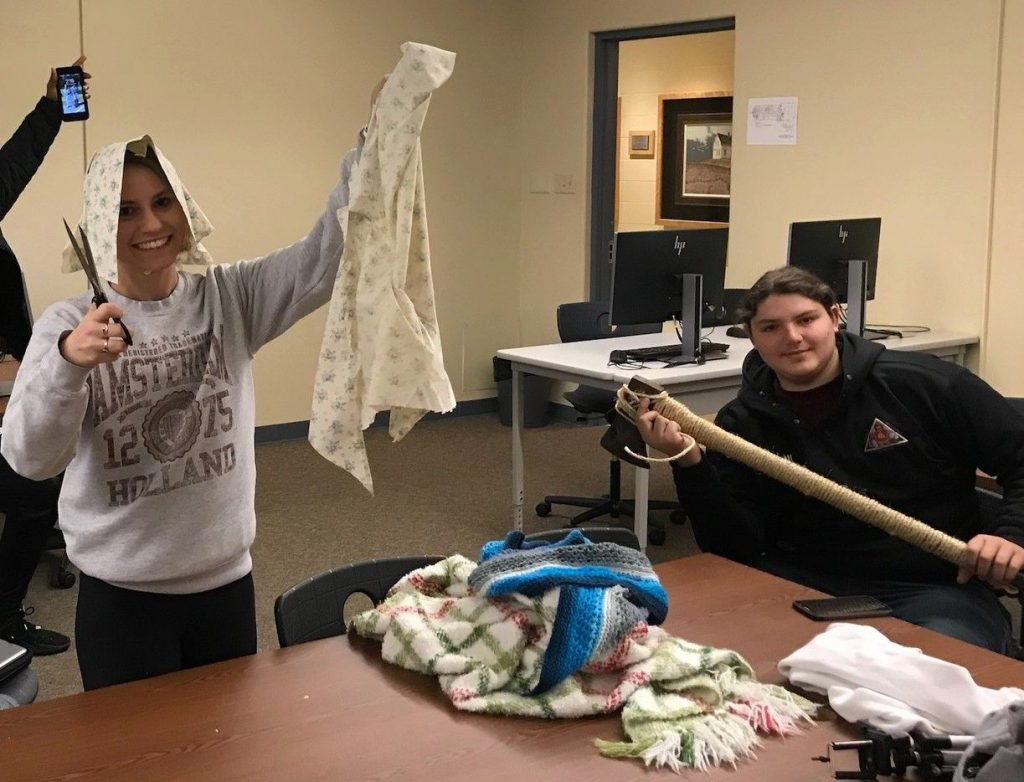 Two students holding movie props: an axe and an 18th-century style women's bonnet and shawl