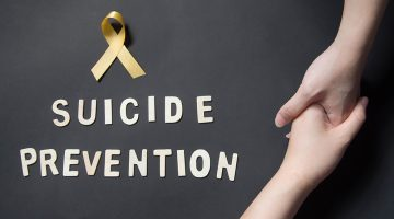 "A yellow ribbon, the words ""suicide prevention"" and two hands grasping each other"