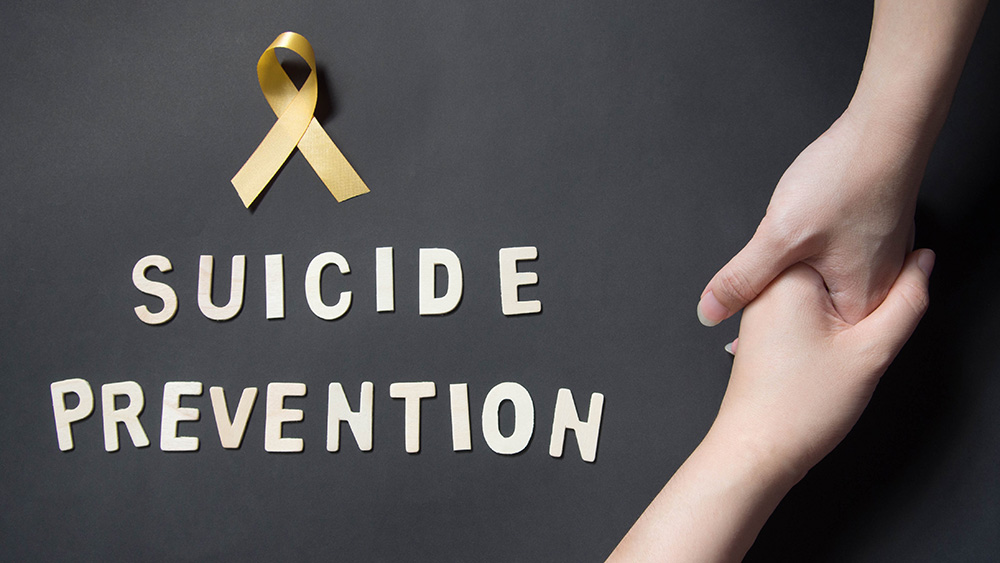 """A yellow ribbon, the words """"suicide prevention"""" and two hands grasping each other"""