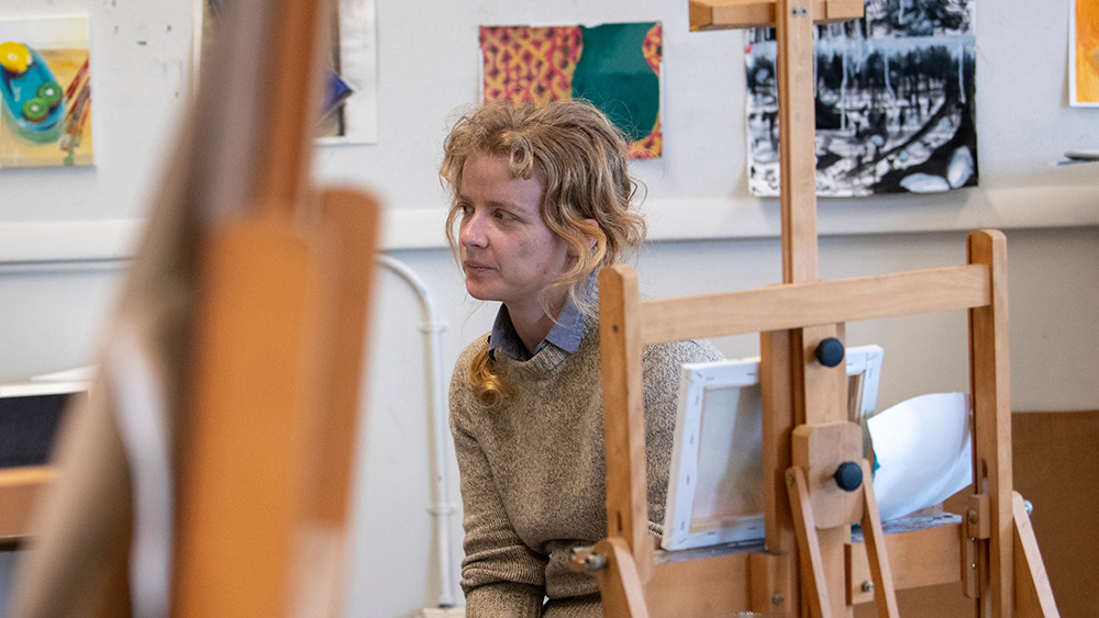 A student in a painting class is looking away from an easel