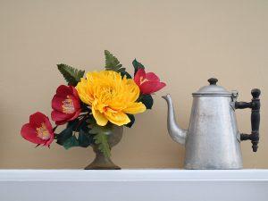 A paper flower bouqet next to a teapot
