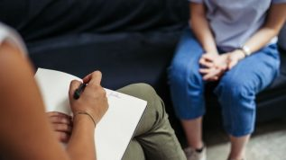 A shot showing the hands and legs of two people in a counseling session