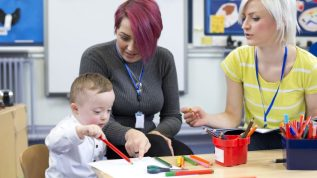 Two women in a classroom with a child who has down's syndrome