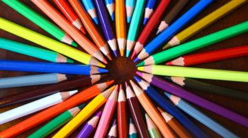 colored pencils arranged in a circle on a black background