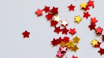 red and gold stars scattered across a white background