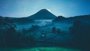 Blues and greys depicting a distant volcano