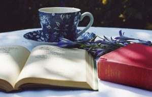 Open book beside a closed one on a tale with a cup of tea