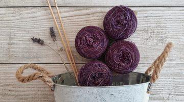 Bowl of purple yarn against a barn wood wall.