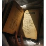 woman's hand on an old book with yellowed pages