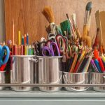 silver containers with paintbrushes, colored pencils, rulers and scissors
