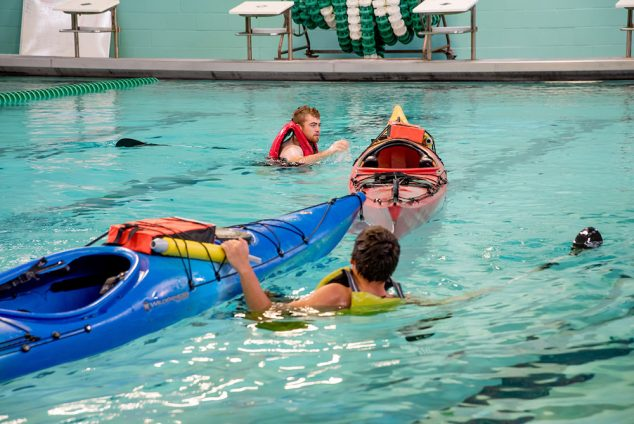 Indoor pool scene. Two individuals are next to their kayaks, wearing life jackets for a kayak rescue class.