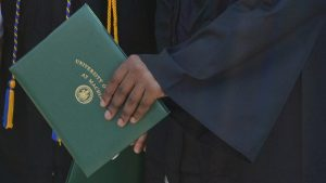 A close-up of someone's hand holding a diploma cover