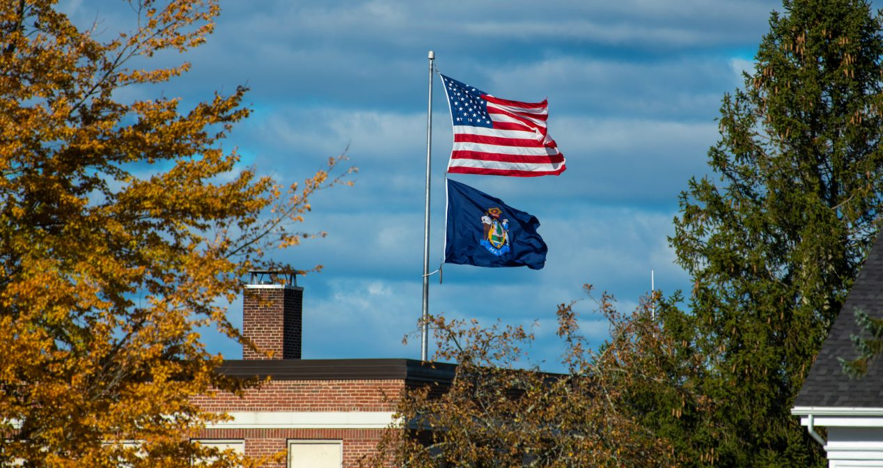 Photo of Powers Hall with Maine State flag and U.S. flag