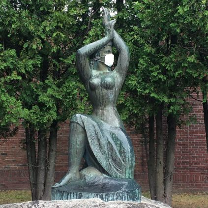 A sea maiden statue wearing a surgical mask