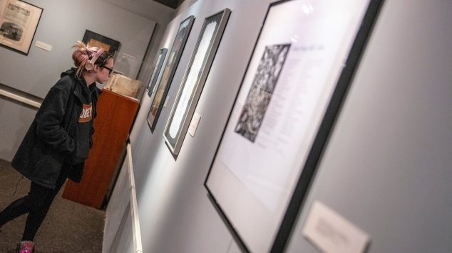A student viewing a wall of framed artwork