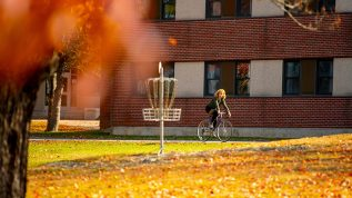 Student riding a bike on campus with autumn colors